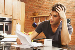 Man looking at paperwork in kitchen.