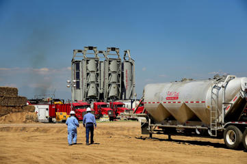 Workers walk towards Halliburton Co. 'sand castles' at an Anadarko Petroleum Corp. hydraulic fracturing (fracking) site north of Dacono, Colorado, U.S., on Tuesday, Aug. 12, 2014.