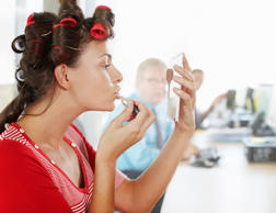 Businesswoman in curlers applying lipstick at her desk