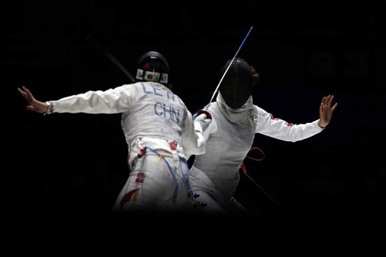 Le Huilin of China (left) and Oh Ha-Na of South Korea compete in the women's foil team final during the 2014 Asian Games.
