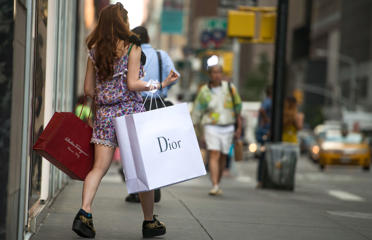 A shopper carries Salvatore Ferragamo SpA and Christian Dior SA bags while walking on Madison Avenue in New York, U.S., on Wednesday, Sept. 3, 2014. The Bloomberg Consumer Comfort Index, a survey which measures attitudes about the economy, is scheduled to be released on Sept. 11.