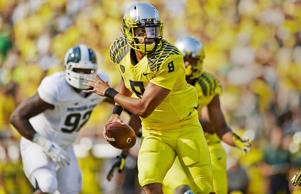 Oregon quarterback Marcus Mariota looks to pass during a game against Michigan State on Sept. 6 at Autzen Stadium in Eugene, Ore.