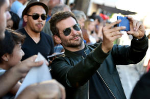 Bradley Cooper takes a selfie with a fan at the premiere of Guardians Of The Galaxy at El Capitan Theatre on Monday, July 21, 2014, in Los Angeles.