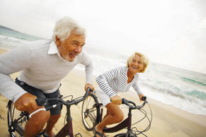 File photo of a senior couple riding bikes on the beach.