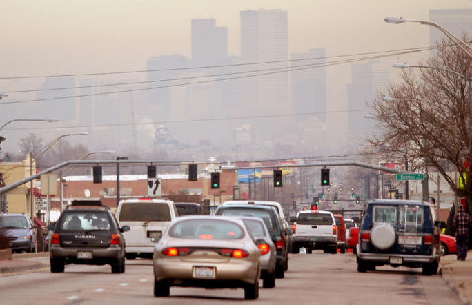 Vehicles head inbound on South Broadway, polluted air obscures the view of the skyline of Denver