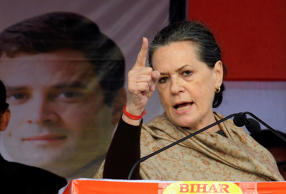File: Chief of India's ruling Congress party Sonia Gandhi addresses a gathering next to a portrait of her son and lawmaker Rahul Gandhi during the foundation laying stone ceremony of a proposed university campus, in the eastern Indian state of Bihar January 30, 2014.