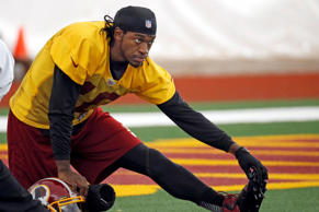 Washington Redskins quarterback Robert Griffin III stretches during an NFL football practice last year in Ashburn, Va.