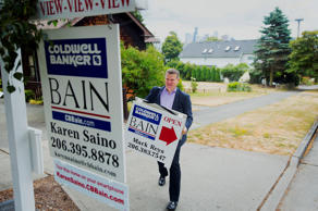 A real estate broker prepares to hang an 'Open House' sign outside of a home for sale in Seattle, Washington.