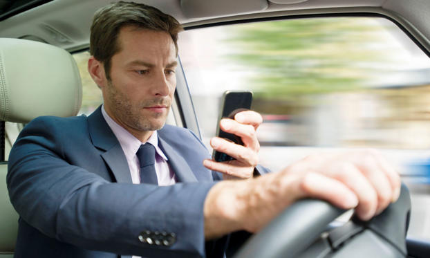 Slide 1 of 13: Man using mobile phone while driving