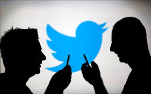 Men are silhouetted against a video screen with a Twitter logo.