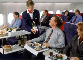 Executives in first class enjoying in-flight meal.