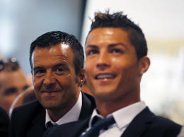 Real Madrid's Ronaldo reacts while watching a video as he sits next to his agent Mendes during a ceremony at Santiago Bernabeu stadium in Madrid