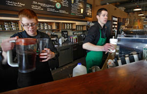 Baristas Lindsey Pringle, left, and Josh Barrow, right, prepare iced and hot Starbucks drinks, at a Starbucks Corp. store in Seattle, Friday, April 27, 2012. Starbucks perked up its net income by 18 percent in its fiscal second quarter, as more customers visited its cafes in most parts of the world.