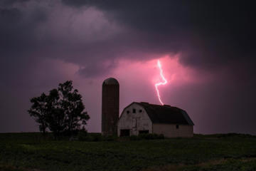 Lighting strikes over a barn surrounded by a soybean crop in Donnellson, Iowa, July 13, 2012.