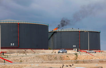 A view shows crude oil storage tanks at an oil refinery in Zawia, 55km west of Tripoli December 18, 2013. Libya is stepping up fuel imports, with four tankers queuing at one port as the OPEC producer's second-largest refinery is running at only half its capacity due to oilfield strikes, a senior official said. A mix of militias, tribesmen and civil servants demanding political rights or a greater share of Libya's oil wealth have occupied several oilfields and ports, cutting exports to 110,000 barrels per day (bpd) from over 1 million bpd in July. The government has struggled to keep the 120,000-bpd refinery in Zawiya operating since protesters in October closed the El Sharara oilfield that feeds it. Since then, Zawiya has runs off existing stocks and supplies from the eastern Brega port, which officials have closed for exports for that reason. To match Interview LIBYA-OIL/REFINERY Picture taken December 18, 2013.