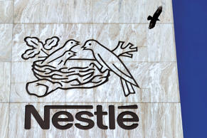 A crow flies above a sign of the world's biggest food company Nestle at their headquarters in Vevey.