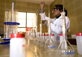 A chemical engineer observes samples of lithium carbonate in a lab.