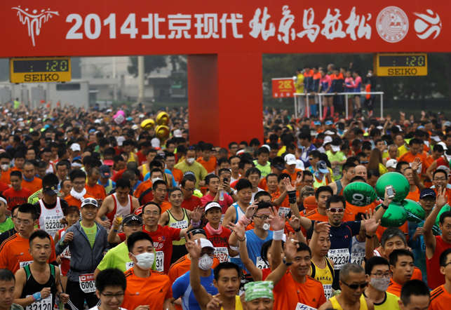 Runners, some wearing masks to protect themselves from pollutants, jog at Tiananmen Square shrouded in haze at the start of 2014 Beijing International Marathon in Beijing, China Sunday, Oct. 19, 2014.