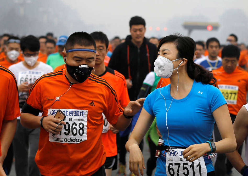 Runners wearing masks to protect themselves from pollutants jog past Chang'an Avenue near Tiananmen Square shrouded in haze while taking part in the 2014 Beijing International Marathon in Beijing, China Sunday, Oct. 19, 2014.