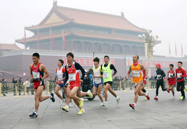 Runners take part in the 34th Beijing International Marathon which began at Tiananmen Square in Beijing on October 19, 2014, with many of the tens of thousands of participants wearing face masks, as the 42-kilometer course ended at the Olympic Park.