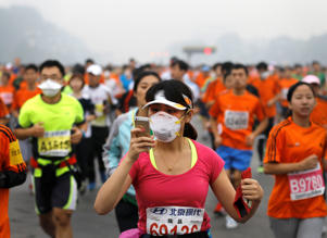 A runner, wearing a mask to protect herself from pollutants, looks at her smartphone as she and others jog past Chang'an Avenue near Tiananmen Square shrouded in haze at the start of 2014 Beijing International Marathon in Beijing, China Sunday, Oct. 19, 2014.