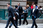 Commuters emerge from the subway and walk to work down Wall Street near the NYSE.