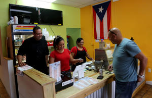 Brian and Marian Dominguez, along with her mother Mariluz Ayala, work behind the counter at Casa Borinquen restaurant in Pembroke Pines, Fla. The couple from Puerto Rico started a food truck about eight months ago to serve Puerto Rican food to the growing community, and it became so popular that three months ago, they opened the restaurant.