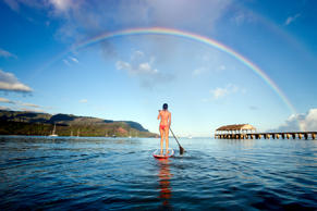 File photo of a woman on a stand up paddle board in Hanalei Bay with rainbow in Kauai, Hawaii.