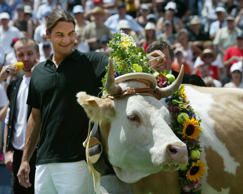 Wimbledon champion Roger Federer (C) poses with cow Juliette, at the Swiss Open in Gstaad, July 8, 2003. Federer received the gift of a cow after being greeted by a standing ovation from 6,000 fans at the Gstaad tournament, where he made his professional debut five years ago. REUTERS/