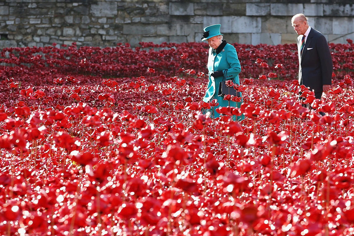 England's Queen Elizabeth II and Prince Philip walk through the Blood Swept Lands and Seas of Red at the Tower of London.