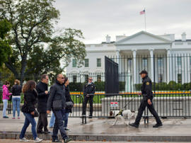 A Secret Service police officer and K9 dog patrol the sidewalk in front of the White House in Washington, Thursday, Oct. 23, 2014.