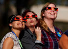 Women gaze up to view a partial solar eclipse outside the Reuben H. Fleet Science Center in San Diego, Calif. on October 23, 2014.