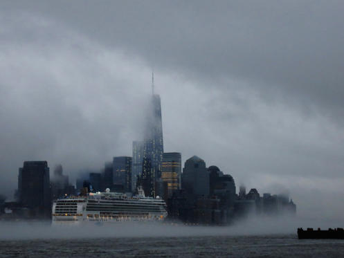 Dia 1 van 20: A cruise ship makes its way past New York's Lower Manhattan as steam rises from the Hudson River.