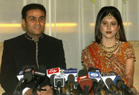 Indian cricketer Virender Sehwag (L) and new wife Aarti Ahlawat address a press conference at their wedding reception in New Delhi, 24 April 2004. The pair were married at a ceremony in India's capital on 22 April, in the residence of the countries Law Minister Arun Jaitley who is also head of the Delhi Cricket Association.