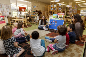 A teacher at a child development center works with prekindergarten students.