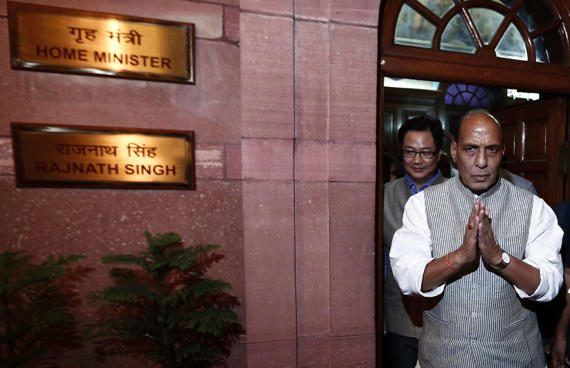 India's Home Minister Rajnath Singh greets the media as he leaves his office.