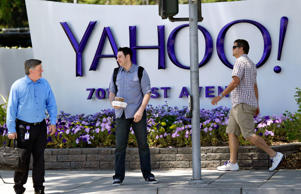 In this June 5, 2014 photo, people walk in front of a Yahoo sign at the company's headquarters in Sunnyvale, Calif. Yahoo Inc. reports quarterly financial results on Tuesday, Oct. 21, 2014.