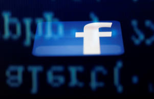 Facebook logo is seen reflected in an iPad screen.