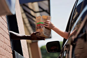 A Burger King employee hands a customer her order at the drive-thru window of a restaurant in Peoria, Ill., on Aug. 26.