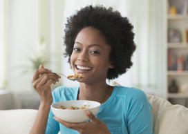 African American woman eating cereal on sofa