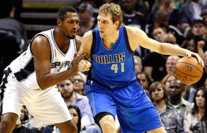 Dallas Mavericks power forward Dirk Nowitzki is defended by San Antonio Spurs po...