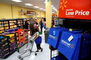 Customers push carts past reusable Walmart shopping bags during the grand opening of a Wal-Mart Stores Inc. location in the Chinatown neighborhood of Los Angeles, California, U.S., on Thursday, Sept. 19, 2013.