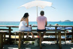 ​Couple in a beach cafe watching people on the beach in Ajaccio, Corsica, France.