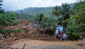 Sri Lankan men stand by a damaged house caused by mudslide at the Koslanda tea plantation in Badulla district, about 220 kilometers (140 miles) east of Colombo, Wednesday, Oct. 29, 2014.