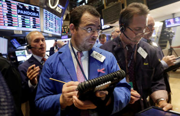 Richard Scardino, center, works with fellow traders on the floor of the New York Stock Exchange, Wednesday, Oct. 29, 2014. Richard Drew/AP Photo  8