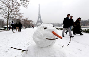 People walk near a snowman as they enjoy the snow near the Eiffel Tower on January 19, 2013 in Paris, France.