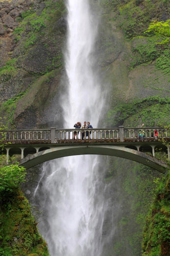 People gather to take photos from the lower falls bridge in front of Multnomah Falls along the Columbia River Gorge Tuesday, June 7, 2011, near Bridal Veil, Ore. States across the west are on the watch for potential flooding in the coming weeks once a record mountain snowpack starts melting and sending water gushing into rivers, streams and low-lying communities. (AP Photo/Rick Bowmer)