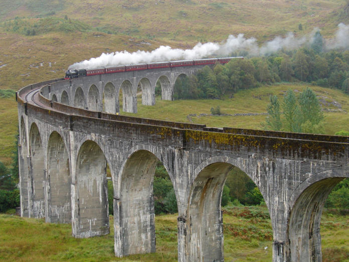 Train Jacobite on Glenfinnan viaduct is going from Fort William to Malaig. Scotland. United Kingdom.