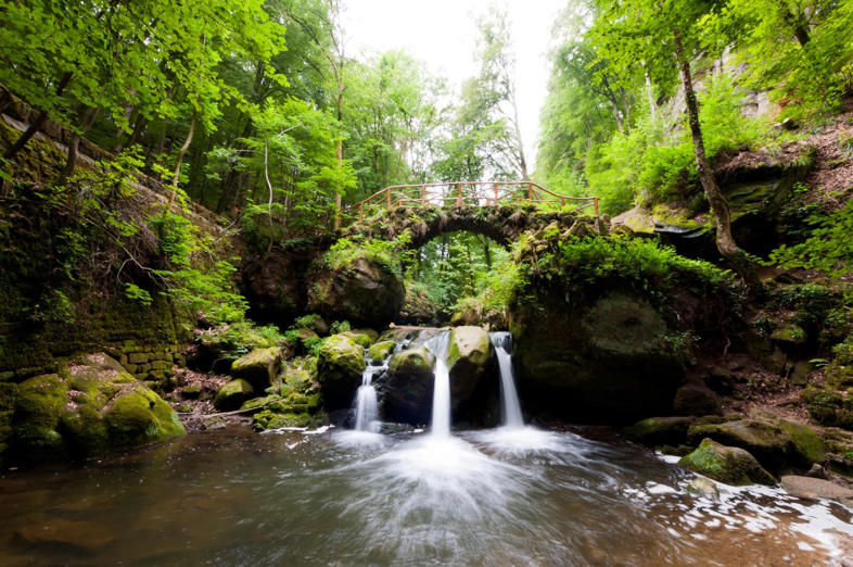 Schiessentumpel in Luxembourg with three streams of water falling down. Old stone bridge crossing over waterfall. Trees and forest in surroundings.