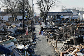This Nov. 14, 2012, file photo shows Louise McCarthy carting belongings from her flood-damaged home as she passes the charred ruins of other homes in the Breezy Point section of the Queens borough of New York. A fire leveled 130 houses in the beachfront community during Superstorm Sandy.